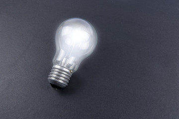 Idea concept word IDEA. Light of bulb on grey background. Low light