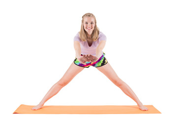 Smiling woman in sportswear stretching back and legs on a mat