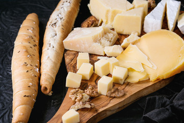 Cheese plate. Assortment variety of cheese with walnuts and bread on olive wood serving board with textile over black ornate and dark blue canvas as background.