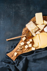 Cheese plate. Assortment of cheese with walnuts, honey from honey dipper on olive wood serving board with textile over dark blue canvas as background. Top view with space.