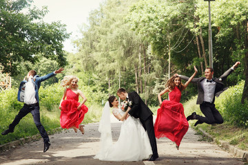 Groomsmen & bridesmaid fun jumping with groom & bride outdoor
