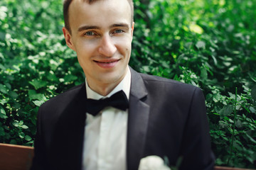 Handsome groom in elegant suit posing on bench face closeup
