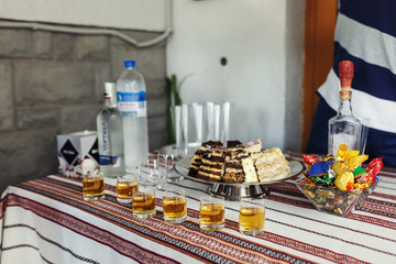 Traditional wedding reception table with alcohol and dessert closeup