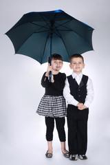 lovely boy and girl standing under umbrella