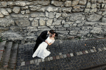 Groom bends bride over standing before old wall