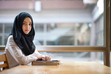 Muslim girl studying at the library.