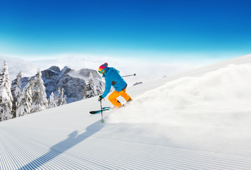 Skier on piste running downhill