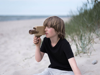 young boy filming on beach