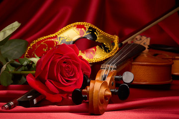 Violin, red rose and theater mask.