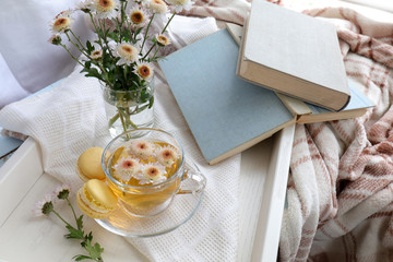 Cup of tea, books, chrysanthemum flowers and macaroons in tray on the table. Cozy home concept