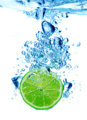 Lime dropped in a water on white background
