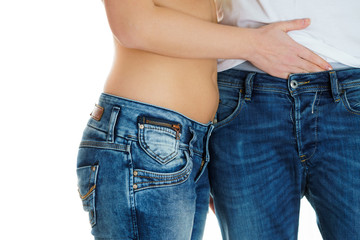 young girl in jeans and a naked stomach touching the genitals of man