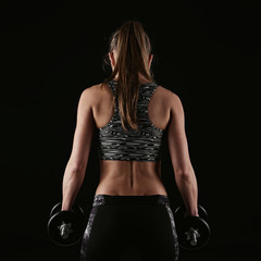 Close up of woman bodybuilder back over black background. Fitness female standing with heavy dumbbells, doing weightlifting exercise.