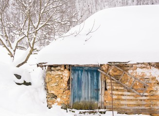 Old wooden cottage covered in snow