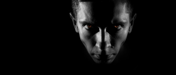 Strict male face in the dark, fiery eyes, a monochrome image, wi