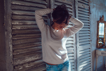 Beautiful young womanl dressed in blank sweatshirt standing on wood wall background. Mock-up.