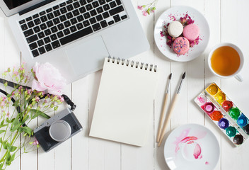 Feminine flat lay workspace with watercolor, paintbrushes, laptop, cup of tea, photo camera and flowers on white wooden table. Top view mock up.