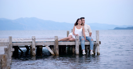 Happy couple sitting on a pier on summer vacation