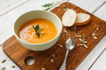 Tasty pumpkin cream-soup with bread and spoon. Top view on orange carrot porridge in bowl on wooden board. Homemade food, vegetarian cuisine, healthy eating concept