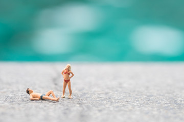 Miniature people in swimsuit relax near swimming pool