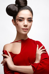 Beautiful girl in a red shirt and shiny hearts on her cheek. Model with a bow on her head and Nude makeup. Image of Valentine's Day. The beauty of the face.