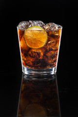 a cocktail of Cola with ice and lime