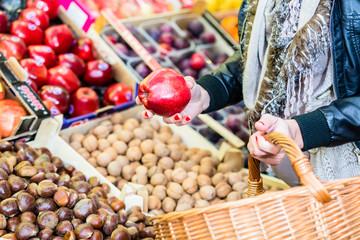 Frau kauft Obst auf Markt am Obststand