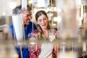 Paar, Mann und Frau, in Elektroabteilung eines Baumarkts sucht Lampen aus
