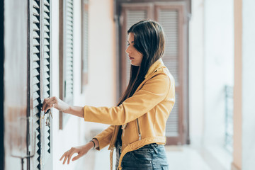 Young beautiful caucasian brown hair woman opening or closing front door - security, safety, lock concept