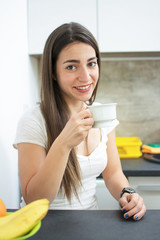 Happy smiling young woman with cup of tea or coffee in the kitchen.