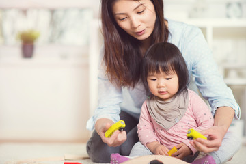 Pretty happy japanese mother play with her little toddler daught