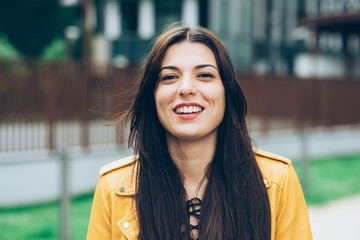 Portrait of young beautiful caucasian brown hair woman outdoor in the city looking at camera smiling - happiness, having fun, serene concept