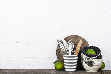 Simple home kitchen still life on a background of bright walls   wooden shelf with bowls  juicy lime and gray striped ceramic mug  cutlery   tools.