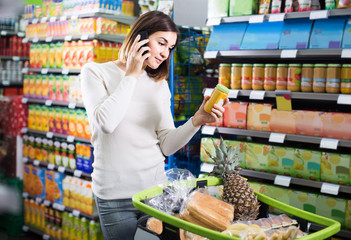 woman consulting on phone about shopping in supermarket