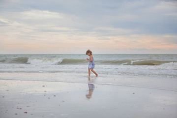Child walking along the beach at sunset searching for seashells and treasure