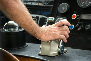 Captain's hand on ship throttle.