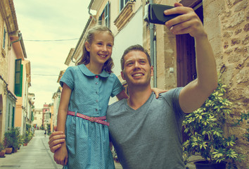 Father and daughter taking selfie in old town. Vintage effect.