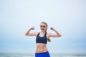 Healthy fitness runner girl showing her biceps