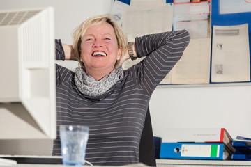 Entspannte zufriedene Frau im Büroalltag am Schreibtisch