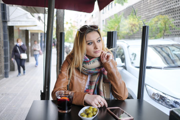 Portrait of beautiful young woman sitting in street cafe.