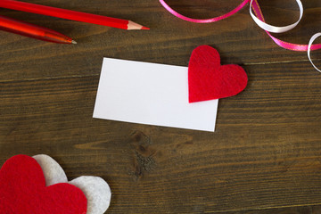 business card with a red heart , pens and tape