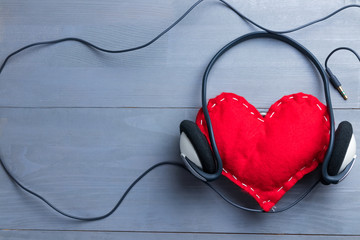 Red homemade heart with headphones on Valentine's Day.