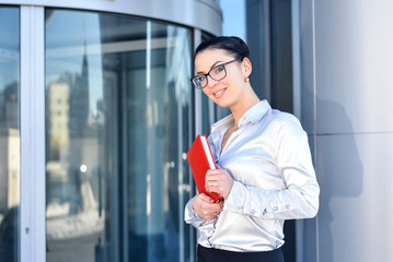 Happy young businesswoman with a notebook in hand on the background of office building