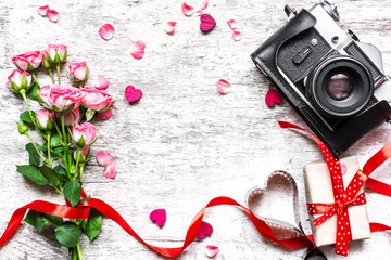 vintage retro camera with pink roses bouquet, red ribbon and gift box