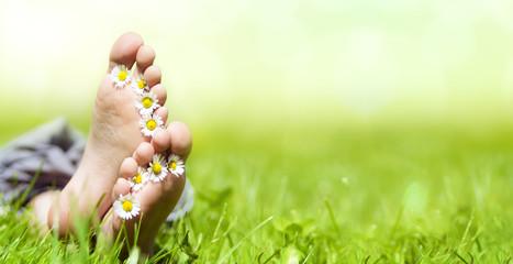 Kinderfüße mit Gänseblümchen auf einer Wiese im Sonnenschein