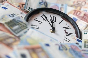 Fuenf Minuten vor zwoelf Uhr / Euro Geldscheine und eine Uhr, die Zeiger stehen fuenf Minuten vor zwoelf.