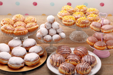 Different types of donuts cakes on wooden table