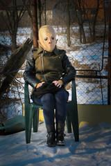 Woman with alien mask in the garden. Winter scene.