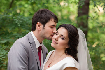Portrait of kissing couple, beautiful bride and groom at wedding day