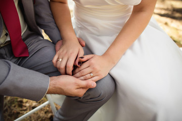 Bride and groom holding hands with engagement rings on fingers at wedding day